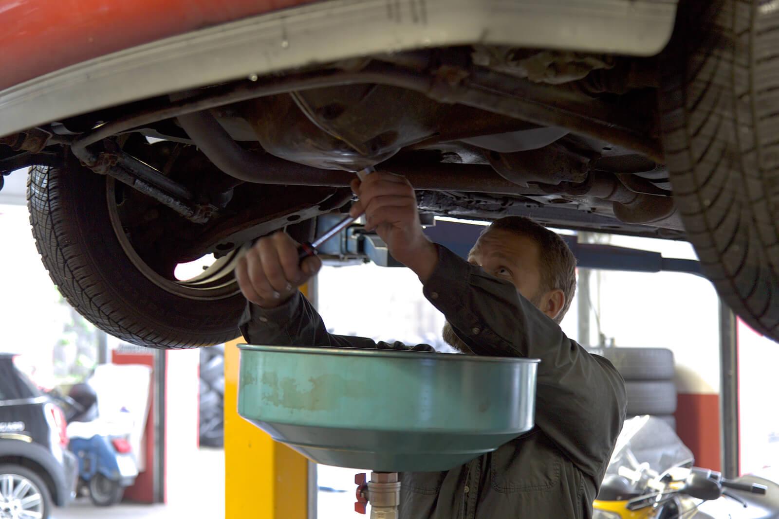 ein Mechaniker wechselt das Öl eines Autos